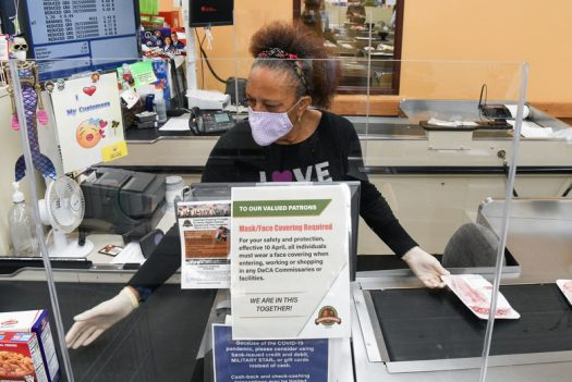 Store clerk Wynetta Johnson scans a customer's purchases. Plexiglass, seen here, is just one of the tools recommended by Barbara Weltman for use in a Covid-19 economy. (Credit: Jill Pickett, U.S. Air Force)